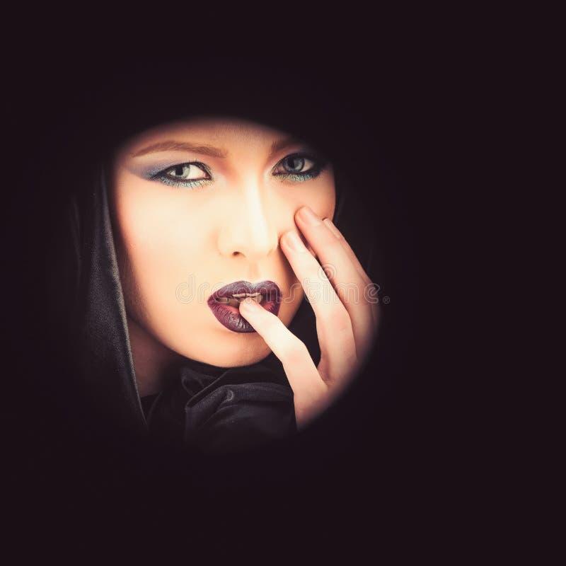 Sguardo e skincare di trucco sensuali della ragazza Donna sexy di madonna in cappuccio nero Modello di moda con trucco della raga fotografia stock libera da diritti
