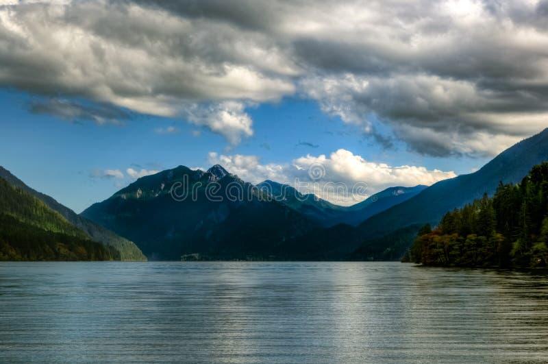 Sguardo fuori attraverso la mezzaluna del lago con le montagne blu profonde scure nella distanza e nuvole e cielo blu lanuginosi  immagine stock libera da diritti