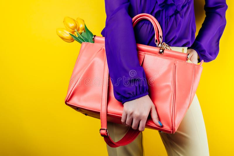 Sguardo moderno ed alla moda di un'attrezzatura d'uso e di tenuta della molla della donna della borsa con i tulipani gialli Colpo fotografia stock