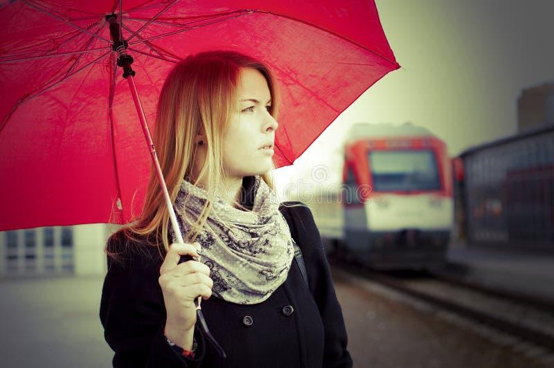 Sguardo sorpreso donna con il treno vicino dell'ombrello fotografia stock