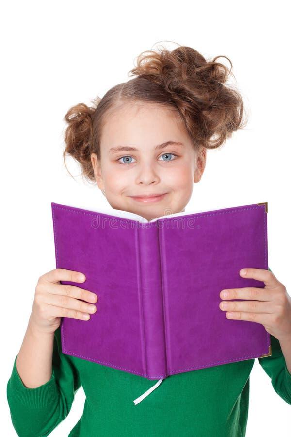 Sguardo sorridente della ragazza dietro il libro fotografie stock libere da diritti