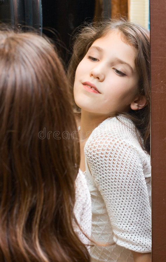 Sguardo teenager della ragazza allo specchio immagine stock