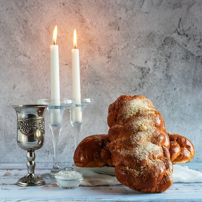 Shabbat Shalom - хлеб challah, вино shabbat и свечи на деревянном столе стоковое изображение