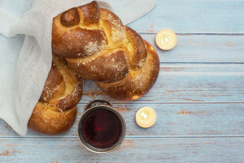 Shabbat Shalom - pane del challah, vino dello shabbat e candele su fondo di legno blu Vista superiore Copi lo spazio fotografia stock