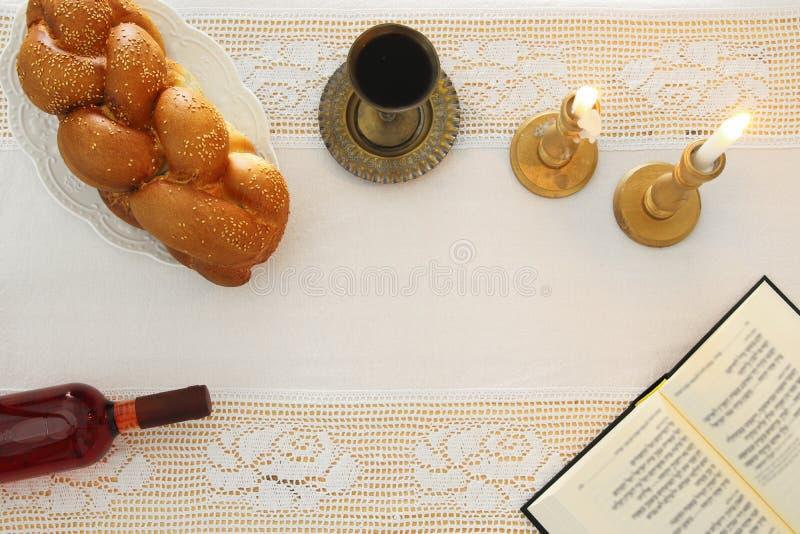 Shabbat wizerunek challah chleb, shabbat wino i świeczki na stole, Odgórny widok fotografia stock