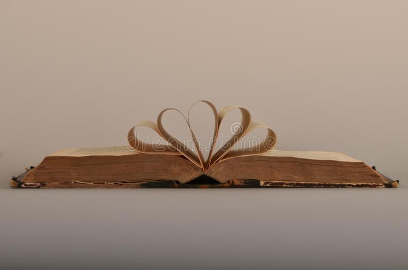 Shabby book with curled pages. Shabby old book in torn cover with curved pages on a gray background stock image