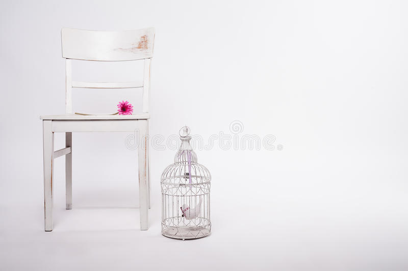 Shabby chair with birdcage and flower stock photos
