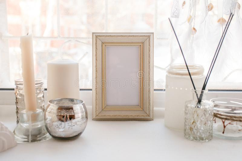 Shabby chic home design. Beautiful decoration table with a candles, dreamcacher, aroma stick and frame with copy space on the. Windowsill, mindfullness relax royalty free stock image