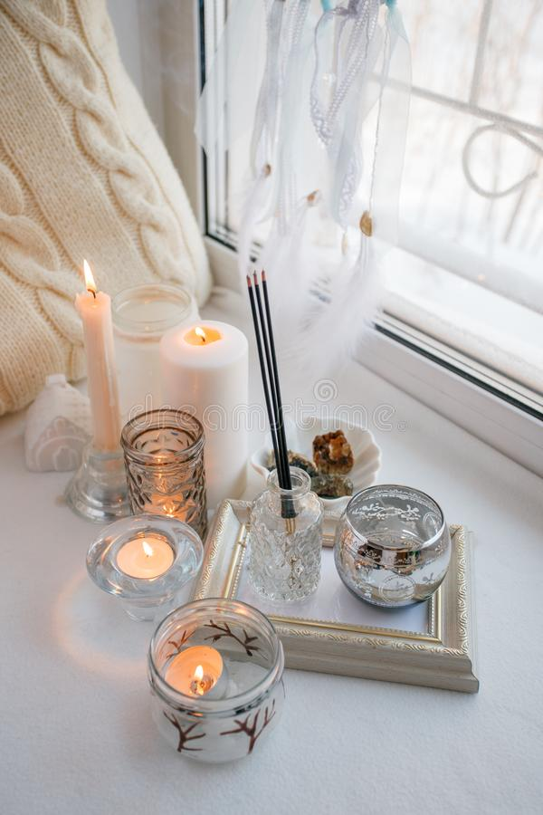 Shabby chic home design. Beautiful decoration table with a candles, dreamcacher, aroma stick on the windowsill, mindfullness relax. Concept stock photography