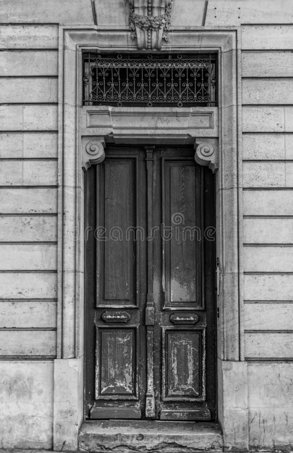 Shabby door entrance of old building in Paris France. Antique wooden doorway and patterned metal grid on window of stone house. stock photo