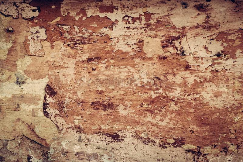 Shabby plaster maroon and orange of wall background. Exterior detail. Decorative brown plaster background texture. stock photo