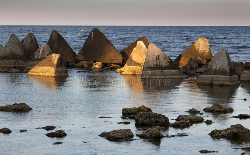 Seascape. Stones and concrete pyramids of light before sunset. Shabla municipality is the most eastern municipality of Bulgaria. The length of the coast is stock images