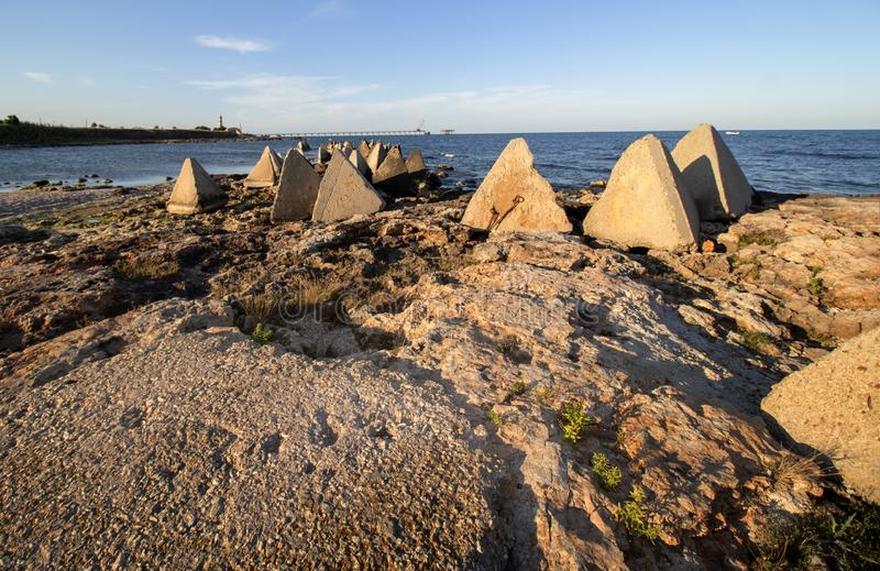Seascape. Rocks and concrete pyramids against the background of the Lighthouse and the Shabla Bridge. Shabla municipality is the most eastern municipality of stock photos