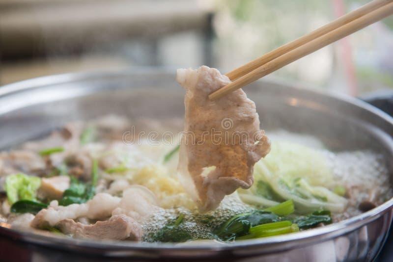 Shabu Shabu of Sukiyaki of hete pot, het varkensvlees van de Handholding gebruikend eetstokjes, Japans voedsel stock foto