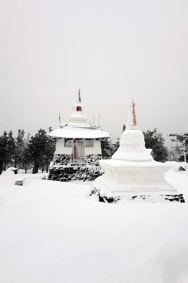 Shad Tchup Ling Buddhist monastery in winter. Stupa and pagoda on top of Kachkanar mountain, Ural, Russia stock image