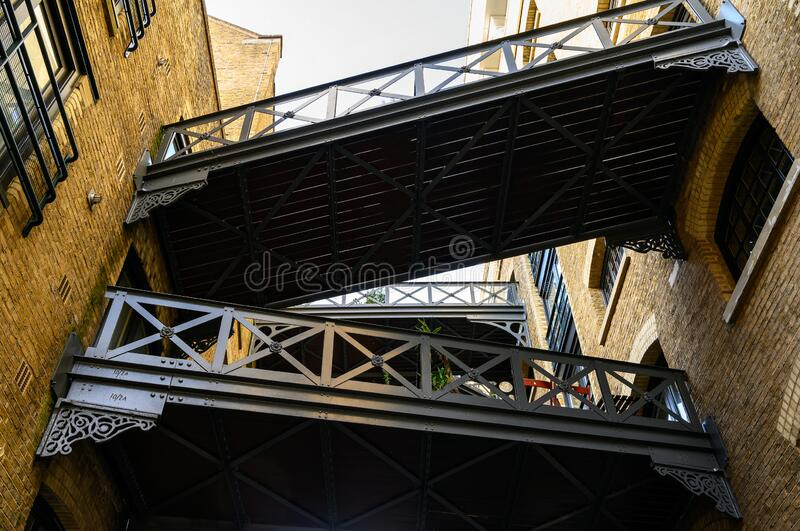 Shad Thames in London, UK. Historic Shad Thames is an old cobbled street known for it`s restored overhead bridges and walkways. This old street is in stock images
