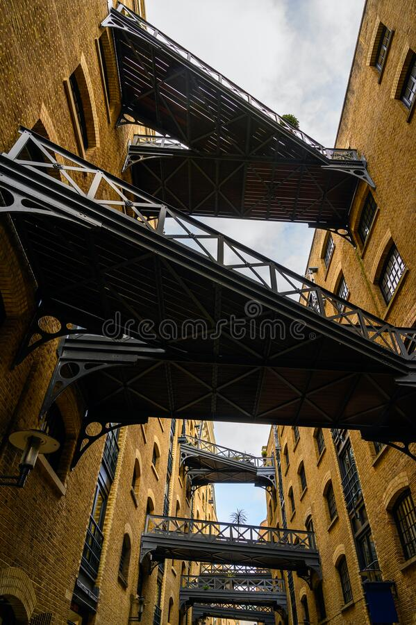 Shad Thames in London, UK. Historic Shad Thames is an old cobbled street known for it`s restored overhead bridges and walkways. This old street is in stock photography