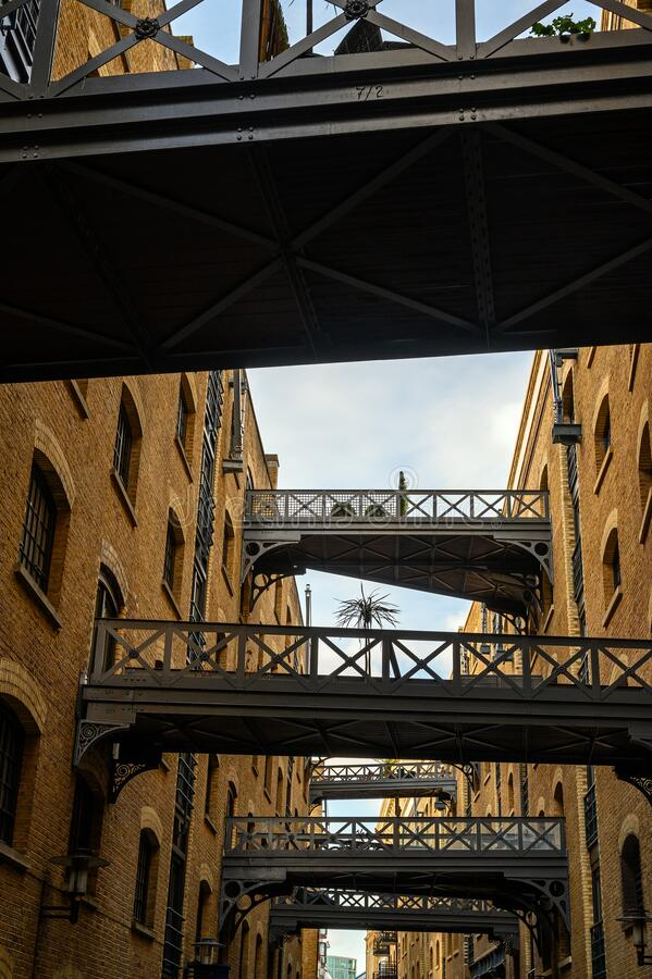 Shad Thames in London, UK. Historic Shad Thames is an old cobbled street known for it`s restored overhead bridges and walkways. This old street is in stock image