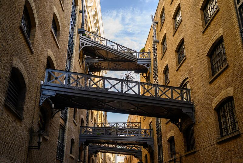 Shad Thames in London, UK. Historic Shad Thames is an old cobbled street known for it`s restored overhead bridges and walkways. This old street is in royalty free stock image