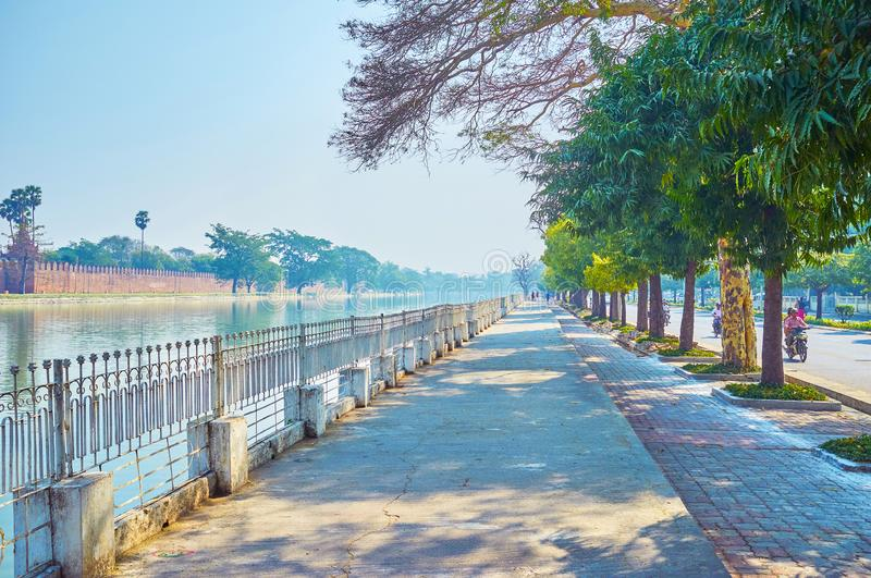 The shaddy street along the moat in Mandalay, Myanmar. MANDALAY, MYANMAR - FEBRUARY 23, 2018: The long shady street along Royal Palace`s moat gives a chance to stock photography