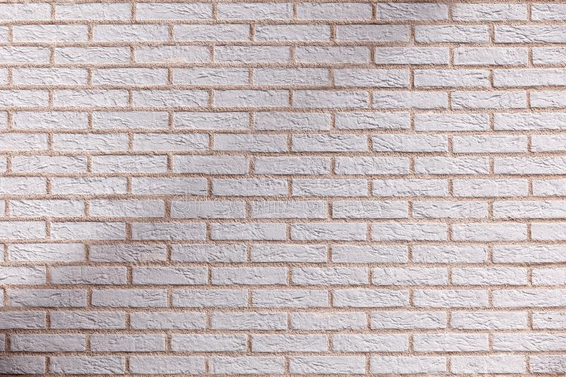 Shaded brick wall. Background beige sand royalty free stock images