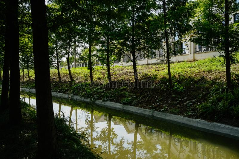 Shaded drain ditch along enclosed buildings on slope in sunny summer afternoon. Shaded drain ditch along enclosed buildings on the slope in sunny summer royalty free stock photography