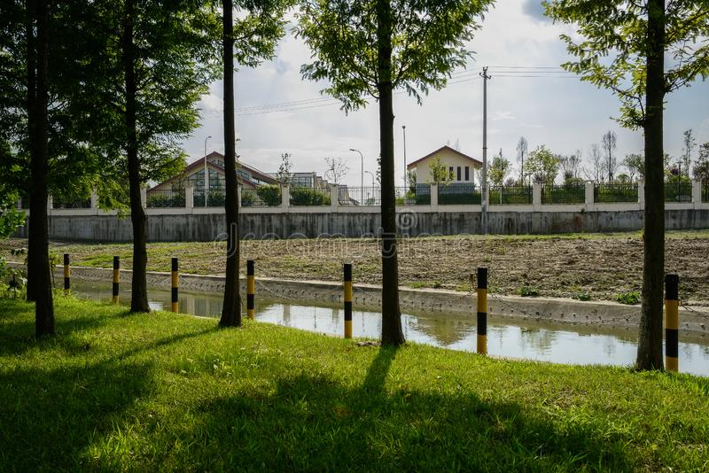 Shaded lawn along irrigation ditch before enclosed buildings on. Shaded grassy lawn along irrigation ditch before enclosed buildings on cloudy summer day,Chengdu stock photo