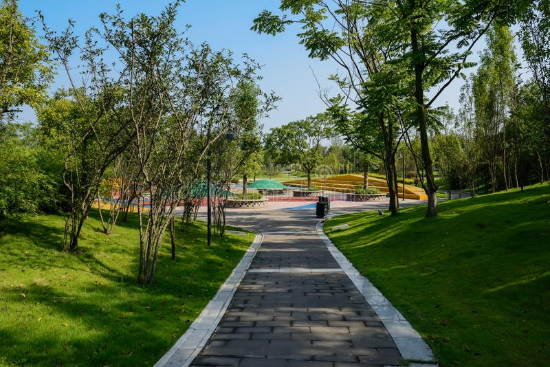 Shaded path in lawn on slope to colorful playground in sunny sum. Shaded path in grassy lawn on the slope to colorful playground in sunny summer morning,Chengdu stock photography