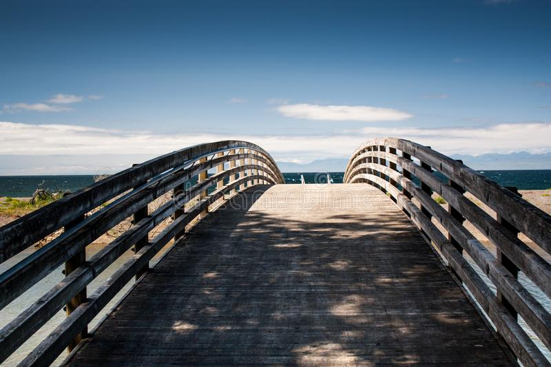 Shaded wooden foot bridge leading to ocean beach royalty free stock photo