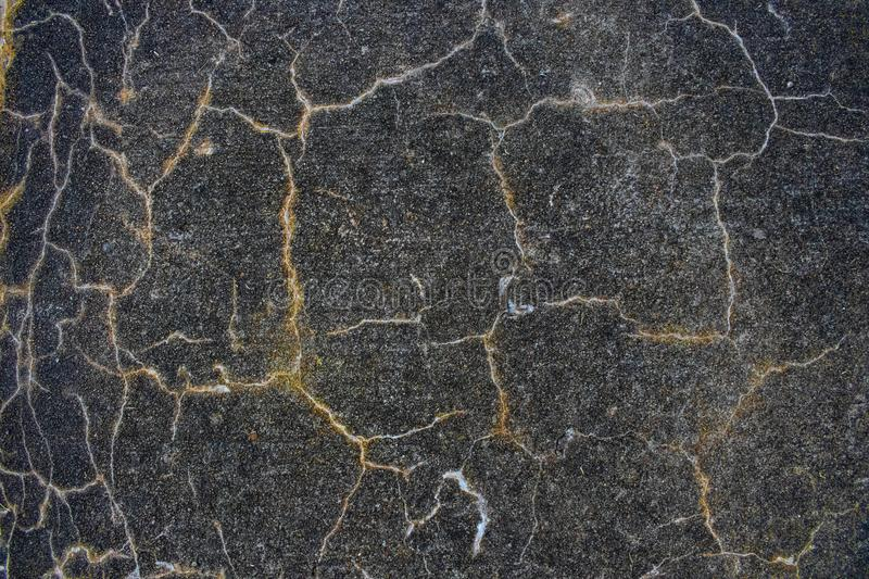 Shades of grey and black and gold and white grunge cracked background. A Shades of grey and black and gold and white grunge cracked background royalty free stock photo