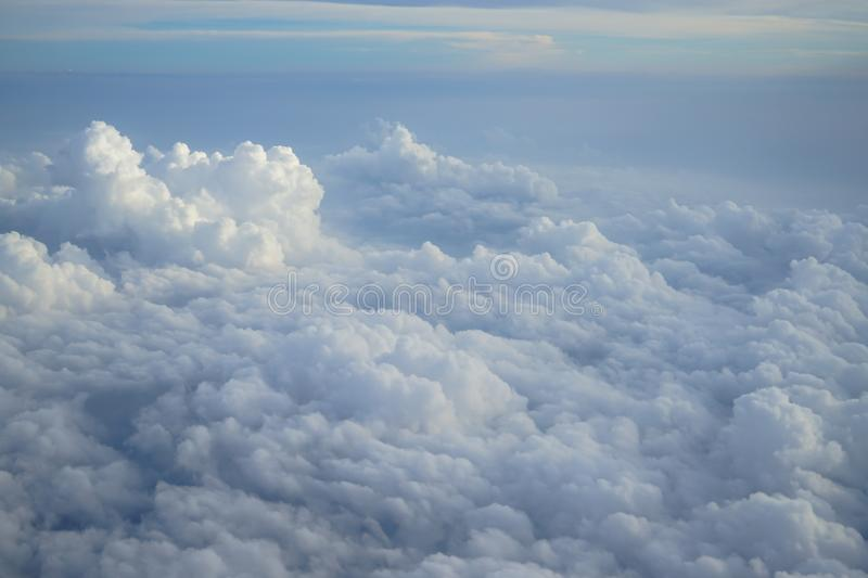 Shades of light blue color sky and constantly change floating white cloudscape view from airplane window. In the morning sunrise royalty free stock image