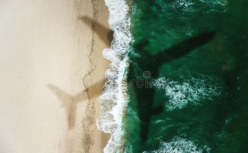 Shadow of an airplane flying over the beach at summer stock images