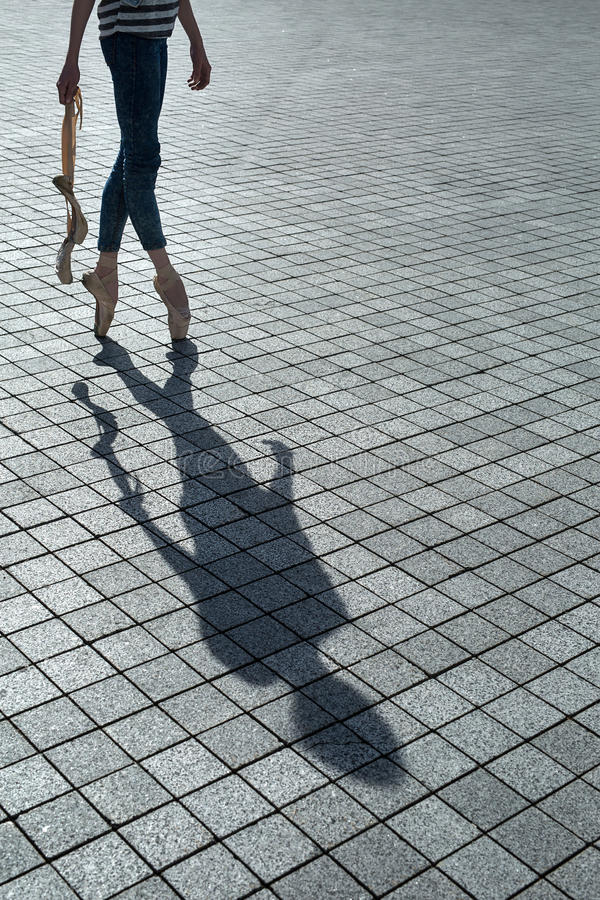 Shadow of the beautiful dancer. Ballerina in blue jeans and pointe stands on tiptoe on a granite tile. In the hands of a couple of unleashed Poitiers. On the stock photo