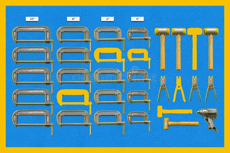 Multiple tools shadow board. Shadow board for C-clamps ,plastic hammers, snips and air impact wrench, some tools are absent form board royalty free stock image