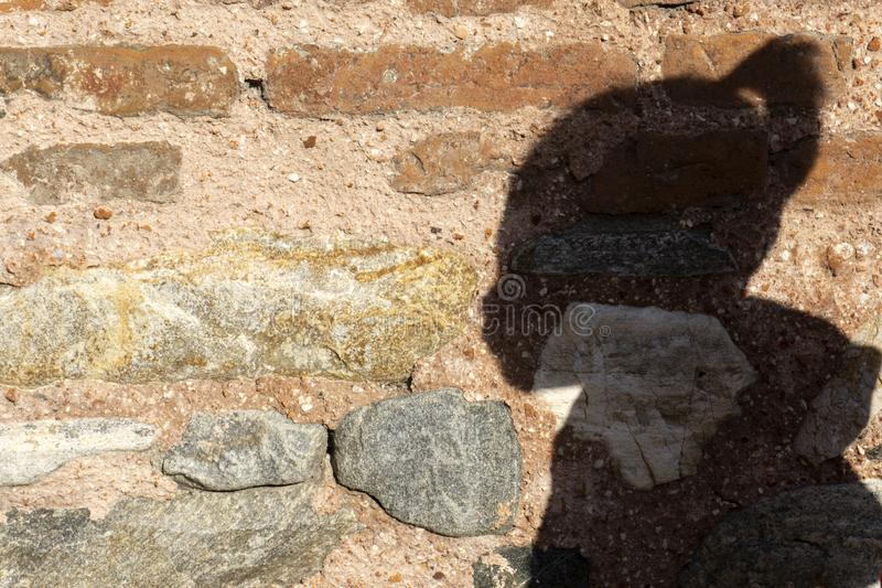 Shadow of a boy on stone wall stock images