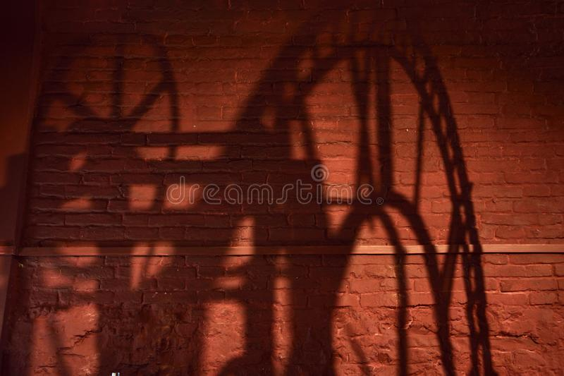 Shadow of a clock mechanism with roman numerals on a brick wall stock photos