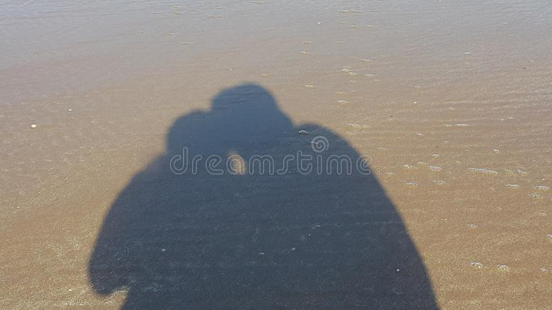 Shadow of a couple on the beach stock photography