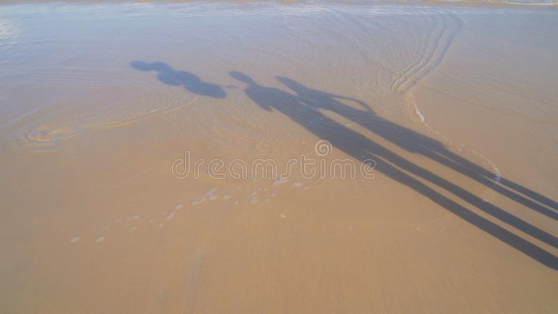 Shadow of couple holding colorful balloons at the beach during travel trip with sand on holidays vacation outdoors at ocean or royalty free stock images