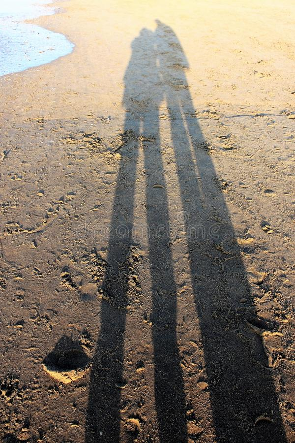 Shadow of a couple on the sand of the beach royalty free stock photos