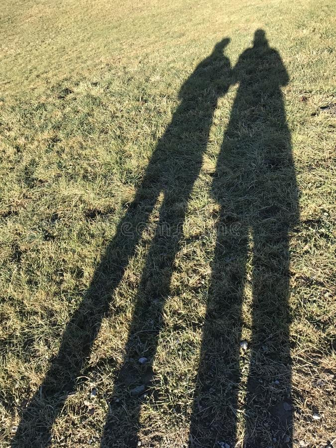 Shadow of a couple cast on frozen yellowish grass stock image