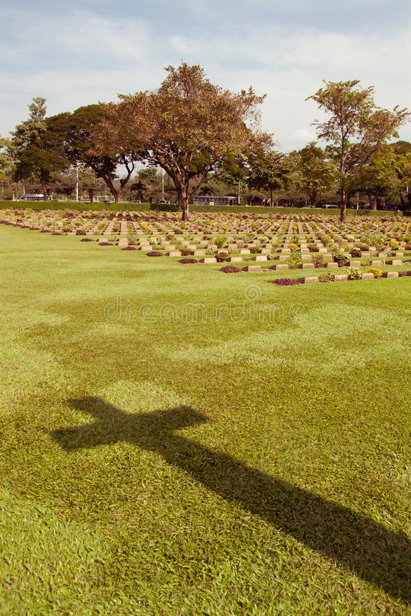 The shadow of a cross looms over grave stones royalty free stock photography