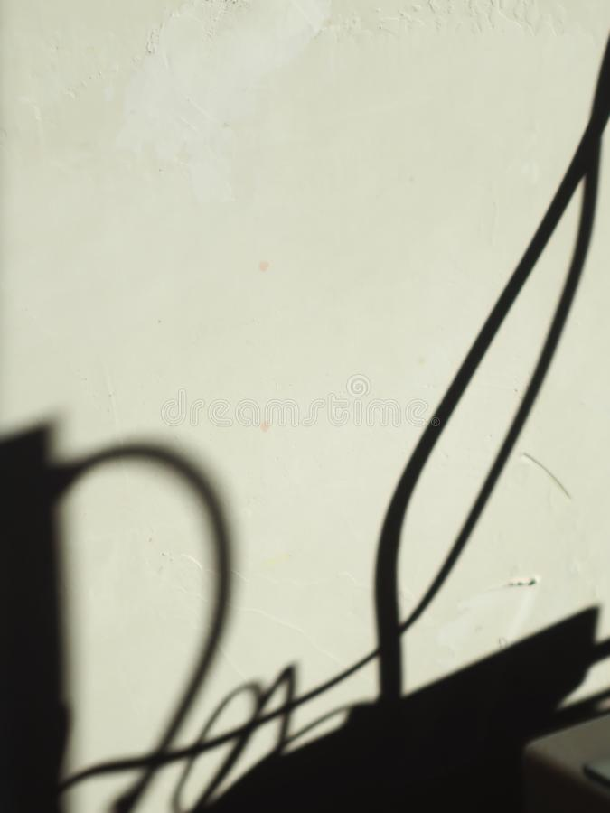 The shadow formed by the wires connecting the computer. A bunch of wires goes to the computer the sun is shining and fancy on the wall out of the shadows stock image