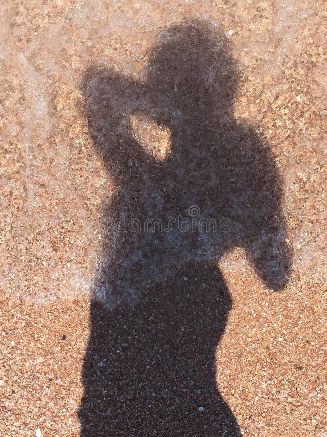 The shadow. A shadow of a girl on sand and coming water royalty free stock photo