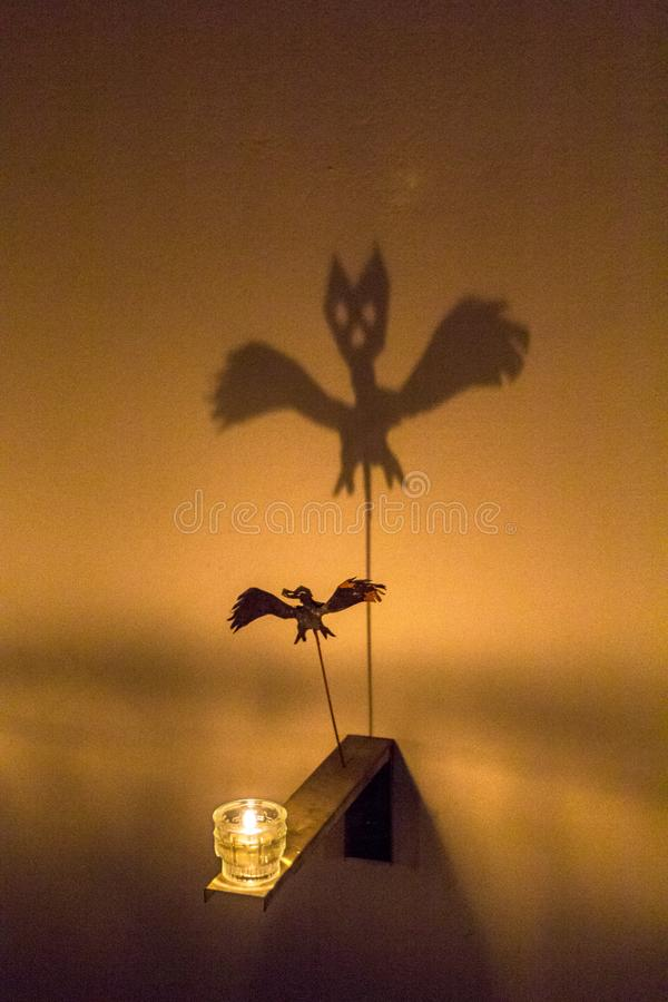 Fabulous shadow of spider bat is reflected on wall from flame of candle. Black Ghost theatre of shadows, Holiday Halloween. royalty free stock photo
