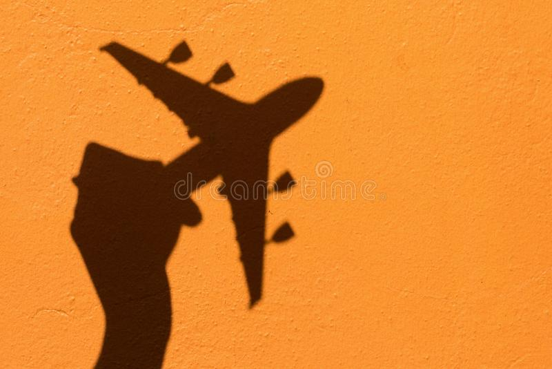 Shadow of Hand holding airplane model on Orange wall background stock images