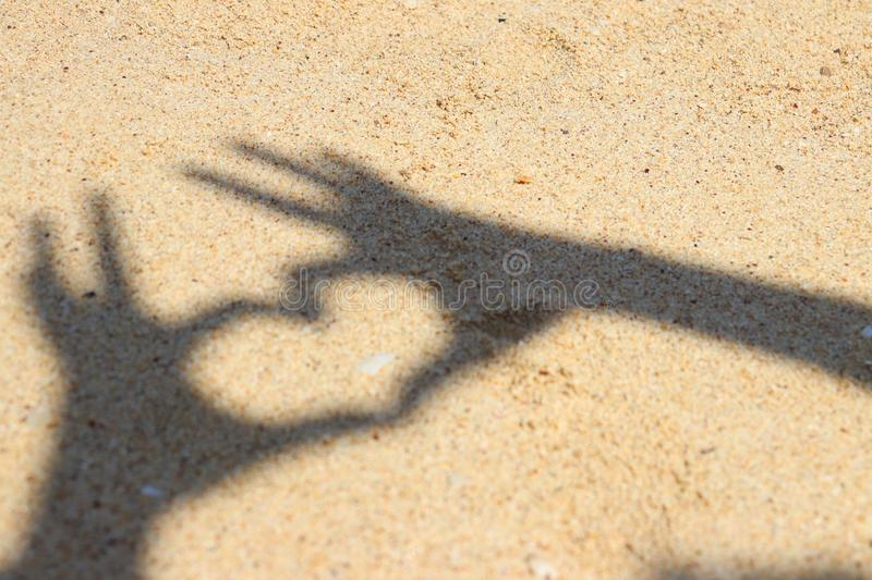 Shadow hands making heart icon on sand at the beach stock image