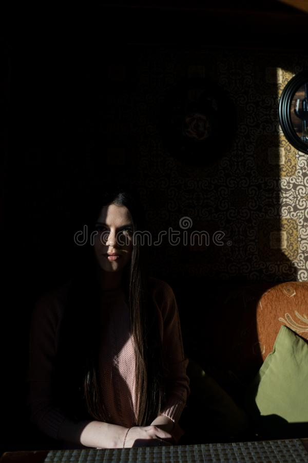 A shadow hides half the face of a girl when she sits in a cafe in the evening stock images