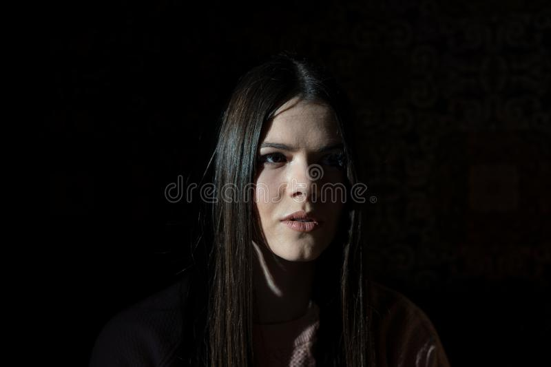 A shadow hides half the face of a girl when she sits in a cafe in the evening royalty free stock photos