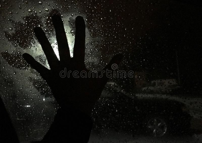 Shadow horror hand on a car glass window royalty free stock images