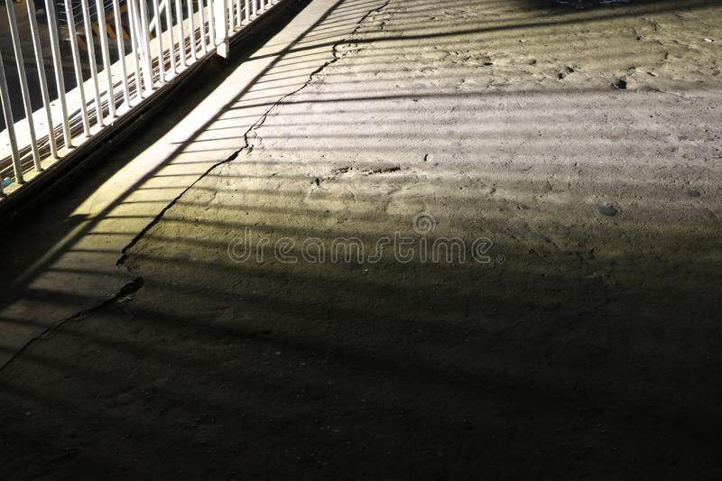 The shadow of the iron bars of the overpass rail on the floor royalty free stock photo